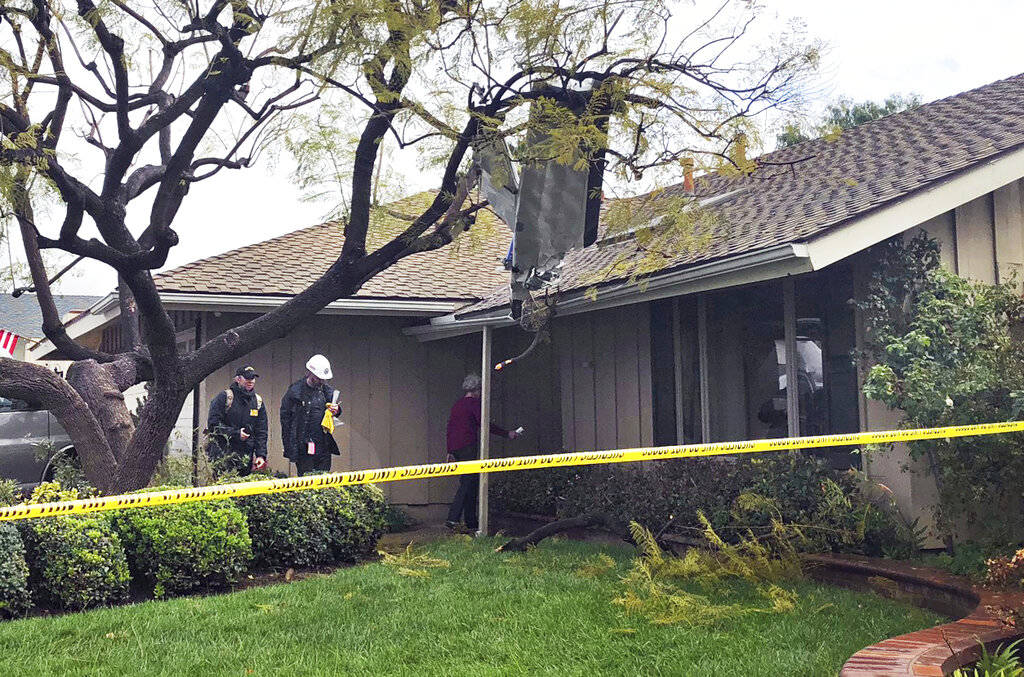 Catherine Paulson, 78, leads investigators to her Yorba Linda, Calif., home that has a piece of aircraft wreckage piercing the roof Monday, Feb. 4, 2019. She said she wasn't home when the plane we ...