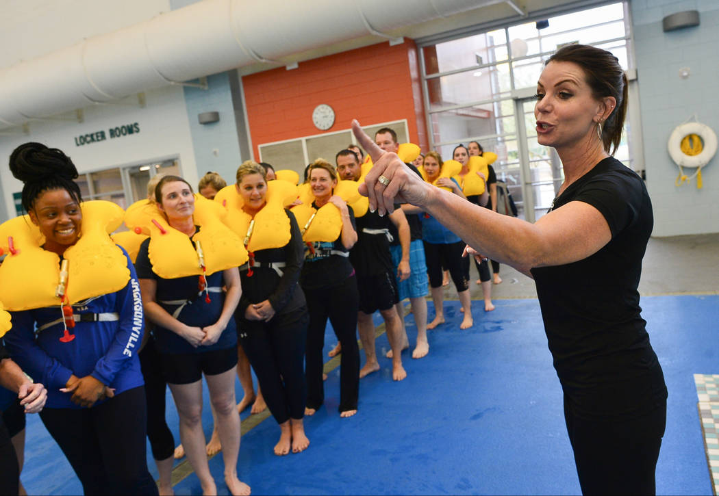Instructor Laurie Fortune, right, based in Sanford, Fla., leads a class of Allegiant Air flight attendant students in water and life raft training at the Heritage Park Aquatic Complex in Henderson ...