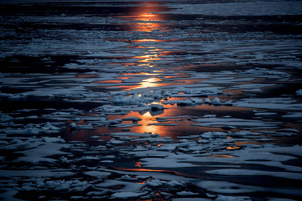 In this July 23, 2017, file photo the midnight sun shines across sea ice along the Northwest Passage in the Canadian Arctic Archipelago. The magnetic north pole is wandering about 34 miles (55 kil ...