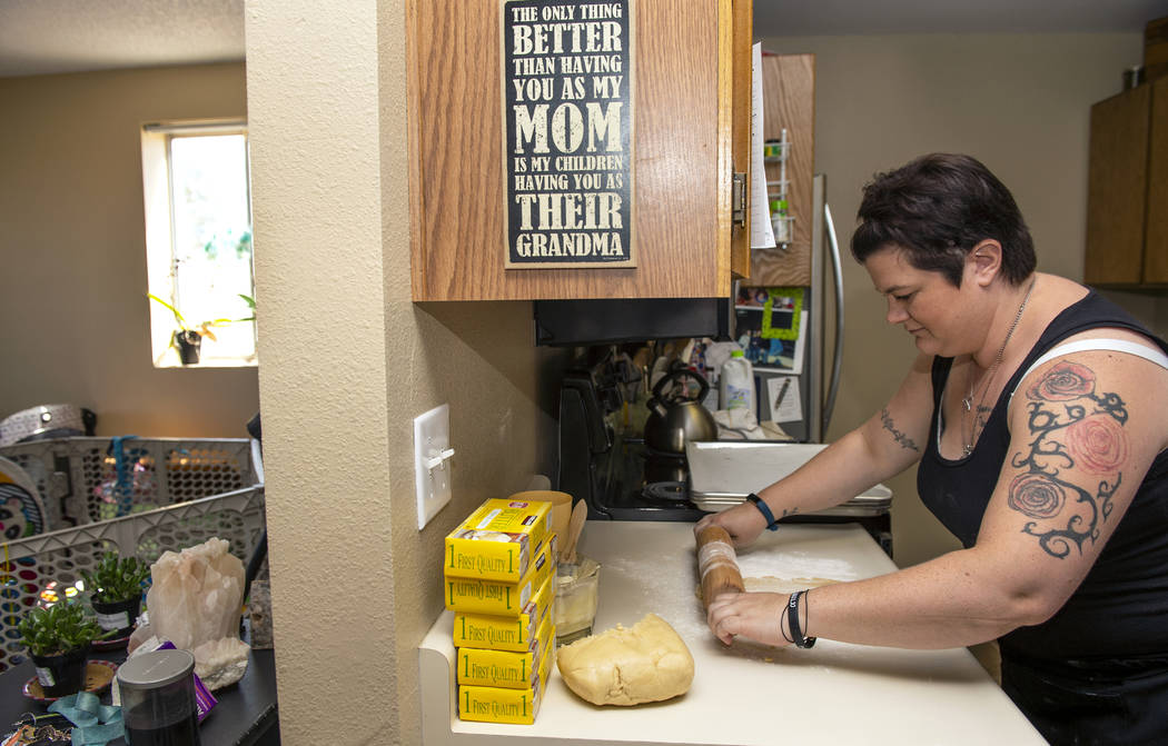 Owner of Cakes, Cookies and Creations Jessica Dejarnett rolls out cookie dough to bake sugar co ...