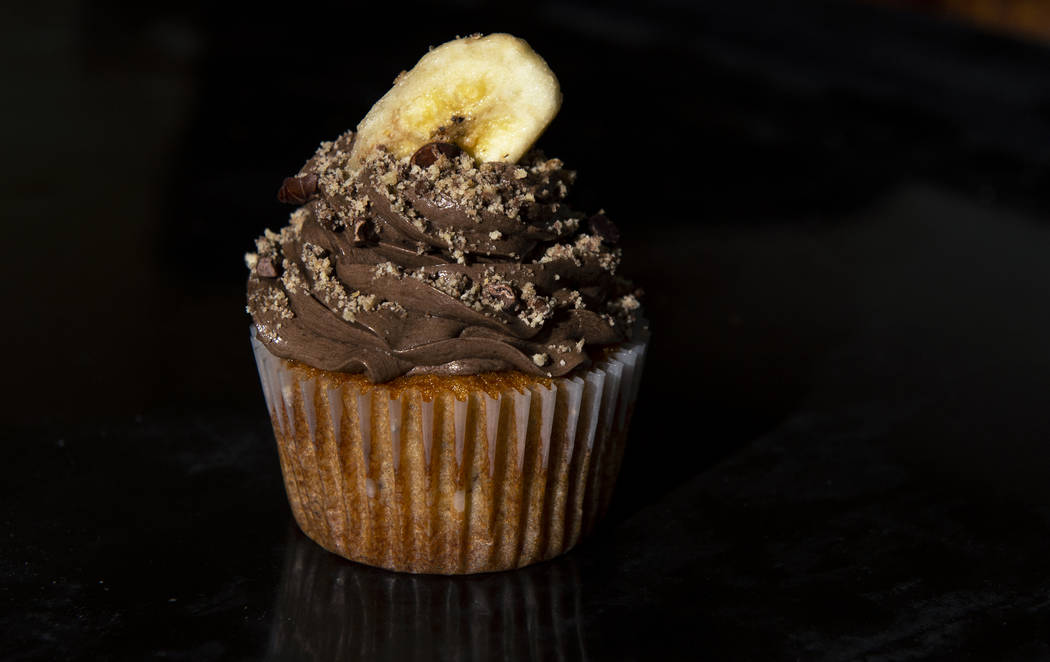 A banana cupcake with chocolate buttercream made by Owner of Cakes, Cookies and Creations Jessi ...