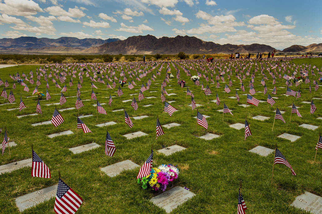 Flags line each gravesite as visitors wander about at the Southern Nevada Veterans Memorial Cem ...