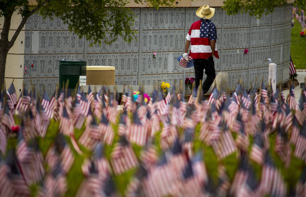 A visitor in a flag-designed shirt pays tribute during Memorial Day before a ceremony at the So ...