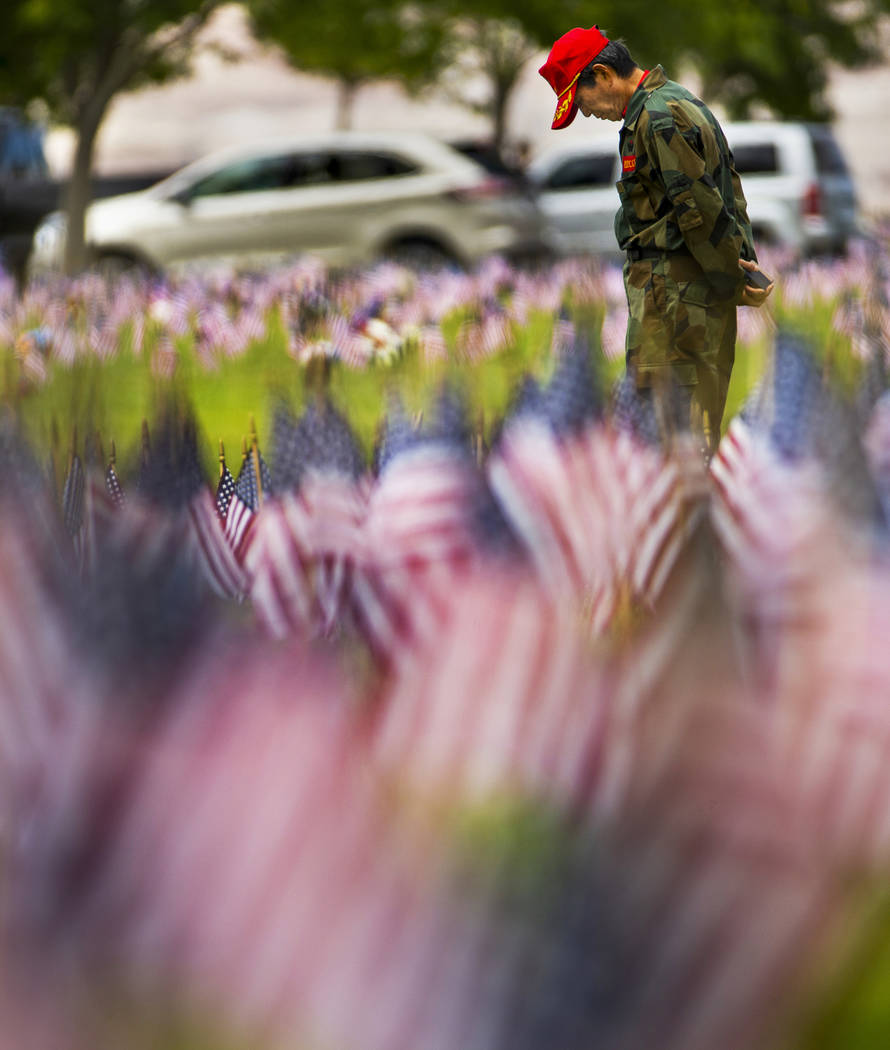 Moosun Lee stops to pay tribute during Memorial Day before a ceremony at the Southern Nevada Ve ...