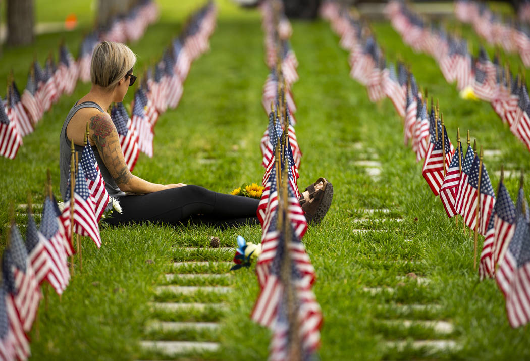 A visitor pays tribute during Memorial Day before a ceremony at the Southern Nevada Veterans Me ...