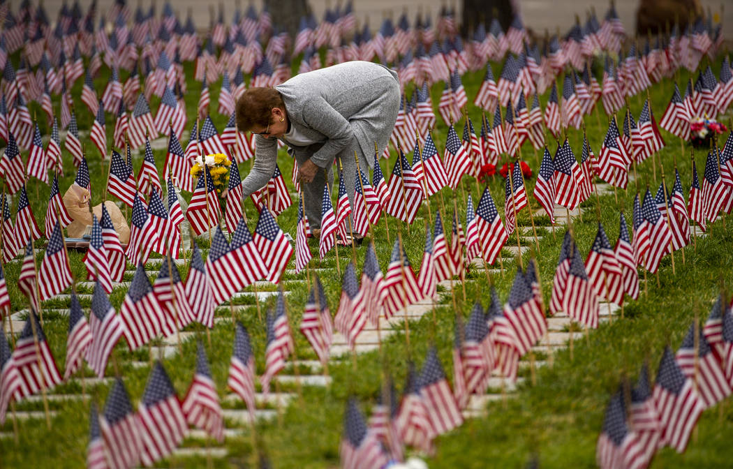 Cecelia Rivera lays flowers at the grave of her father Norman Mitchell on Memorial Day before a ...