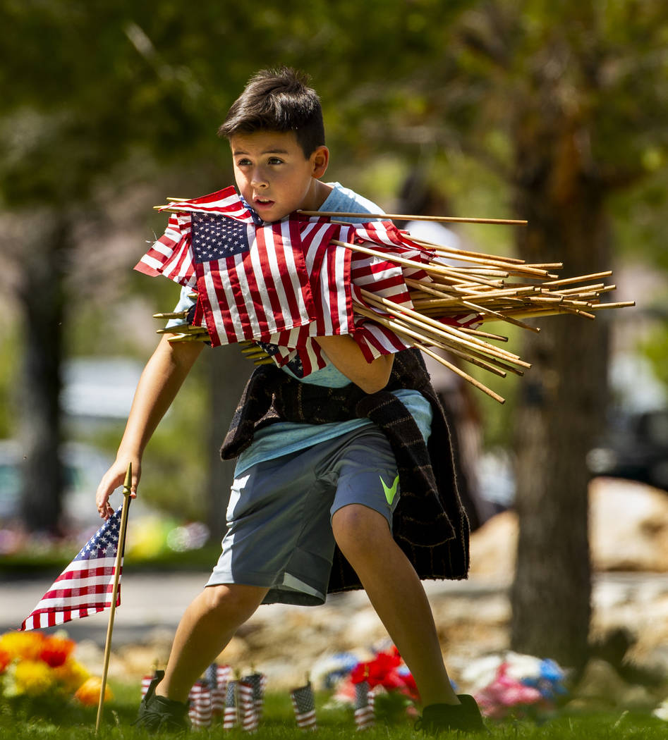 Baron Petersen, 10, helps to gather flags following a Memorial Day ceremony at the Southern Nev ...