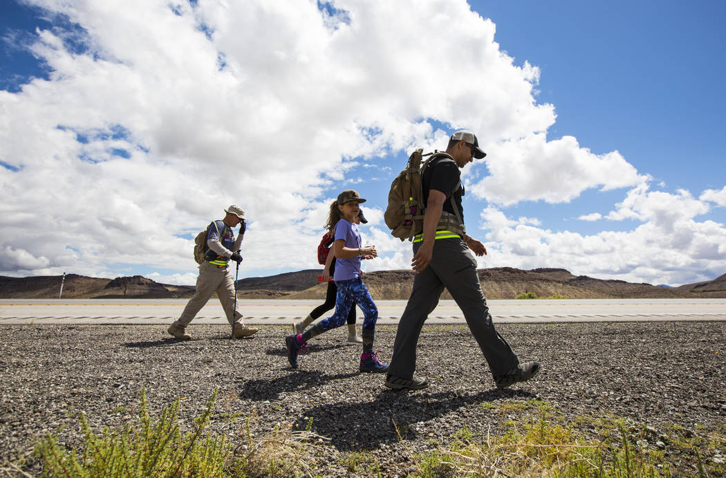 Navy veteran Jelani Hale, of Las Vegas, right, walks with daughter Jet, 9, center, and retired ...