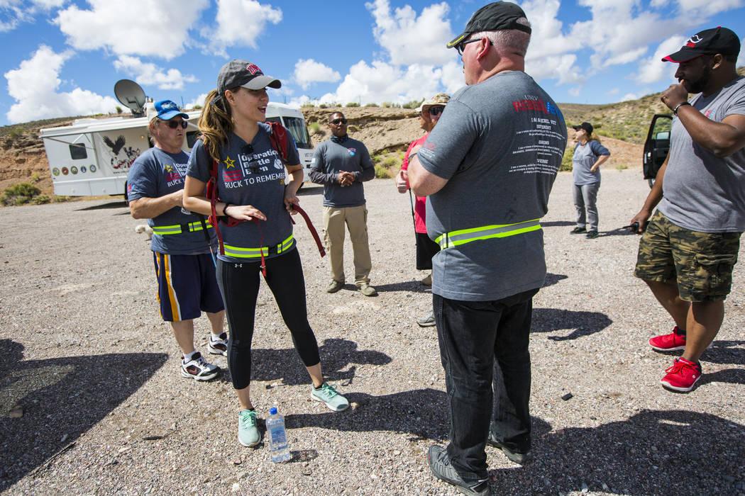 Volunteer Kaci Schroeder, left, of Las Vegas, straps on a rucksack containing dog tags after a ...