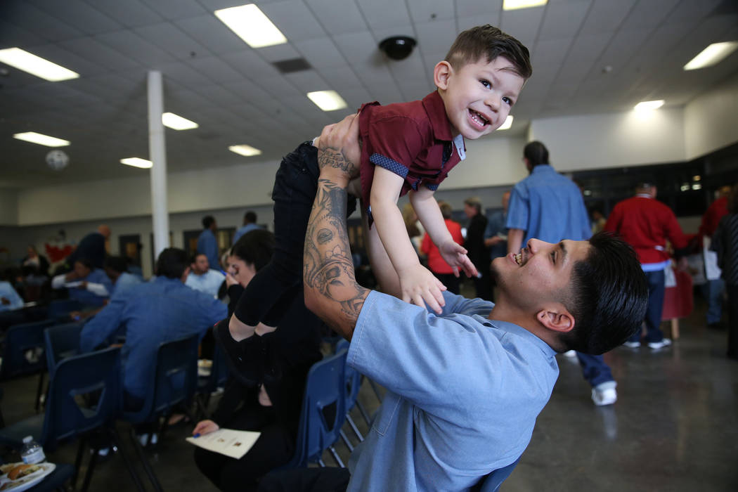 Inmate Anthony Caubet, 22, lifts his son Alexander, 2, following his graduation from the Youthf ...
