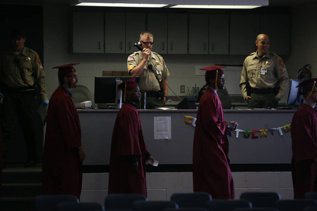 Prison guards watch over inmates as they make their way to their graduation at the High Desert ...