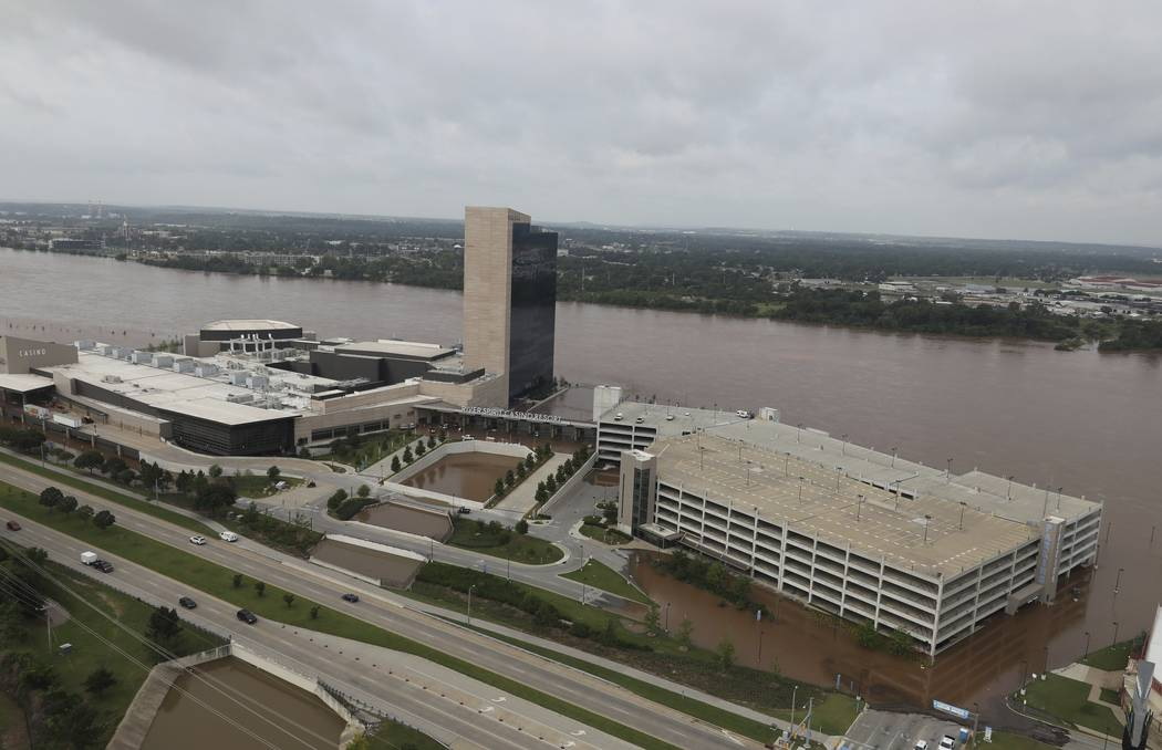 Floodwaters cover the parking area of River Spirit Hotel and Casino on the Arkansas River on Fr ...