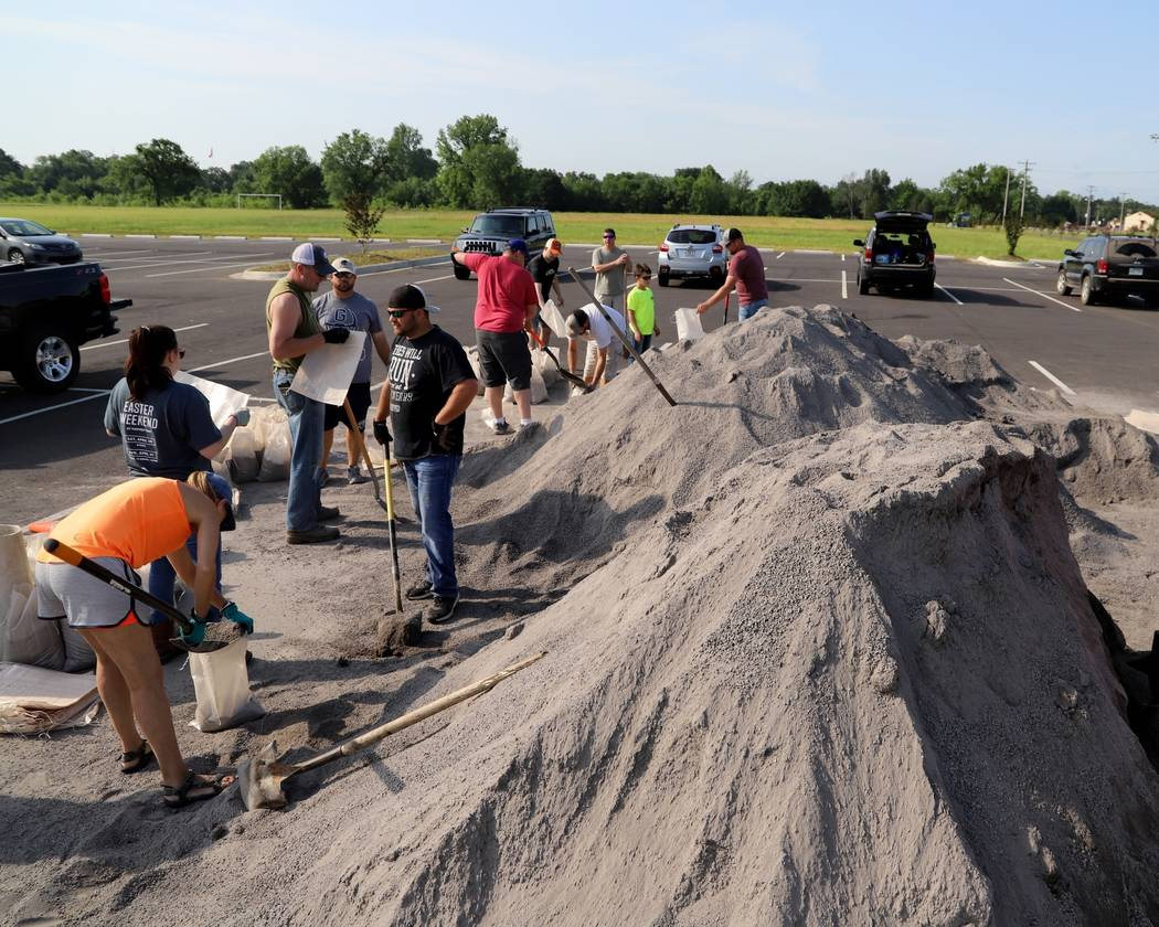 Volunteers fill sand bags at the soccer field parking lot in Chaffee Crossing, Ark., Saturday, ...
