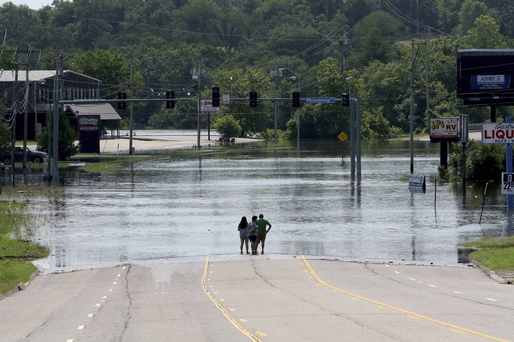 People stand in the middle of Rogers Avenue and look out over the flooded Massard Creek at the ...