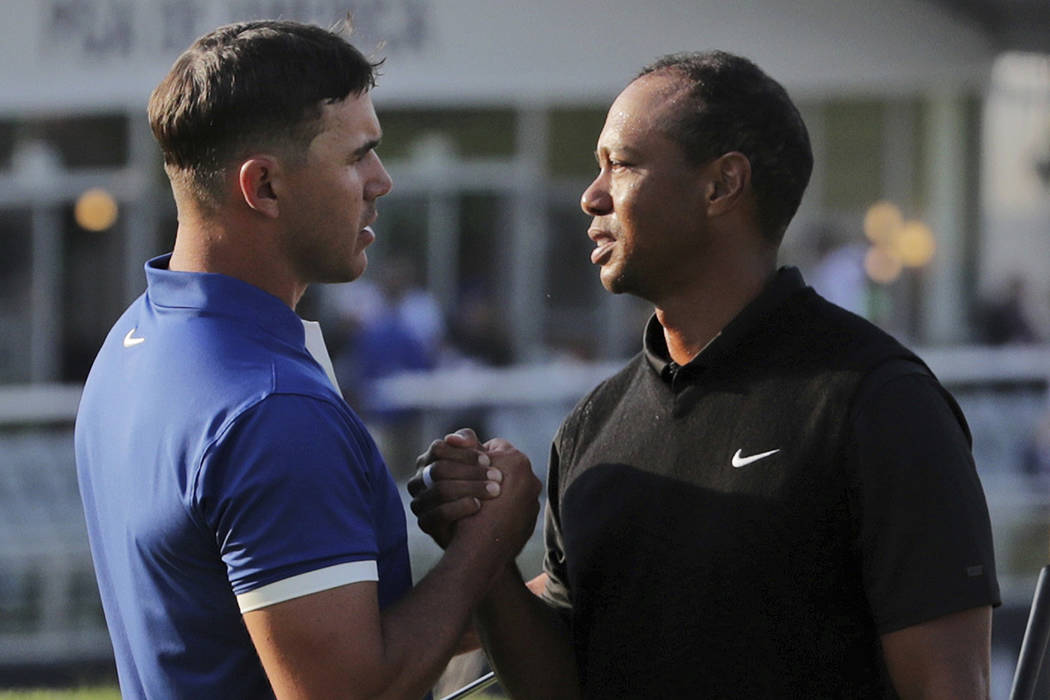 Brooks Koepka, left, shakes hands with Tiger Woods after finishing the second round of the PGA ...