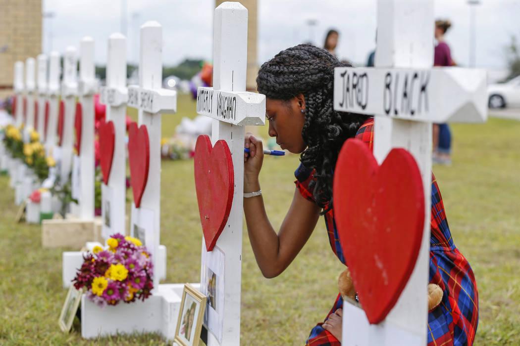 Santa Fe High School freshman, Jai Gillard writes messages on each of the 10 crosses representi ...