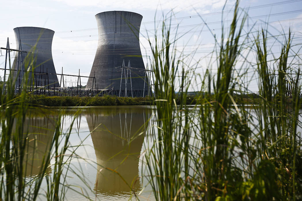 FILE - In this Wednesday, Sept. 7, 2016 file photo, two cooling towers can be seen in the refle ...