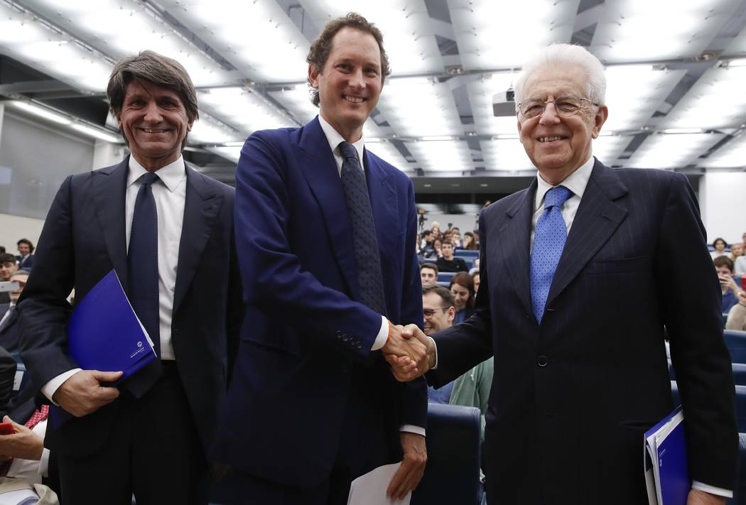 FCA Chairman John Elkann, center, shakes hands with former Italian Premier Mario Monti, right, ...