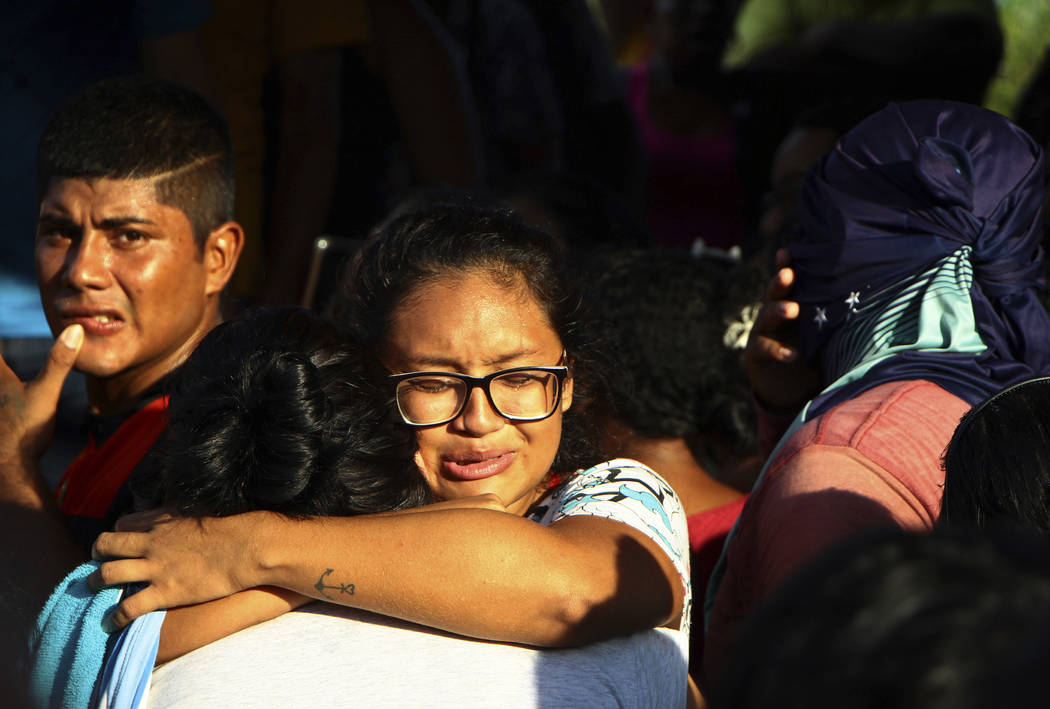 Women embrace outside Anisio Jobim Prison Complex after a deadly riot erupted among inmates in ...