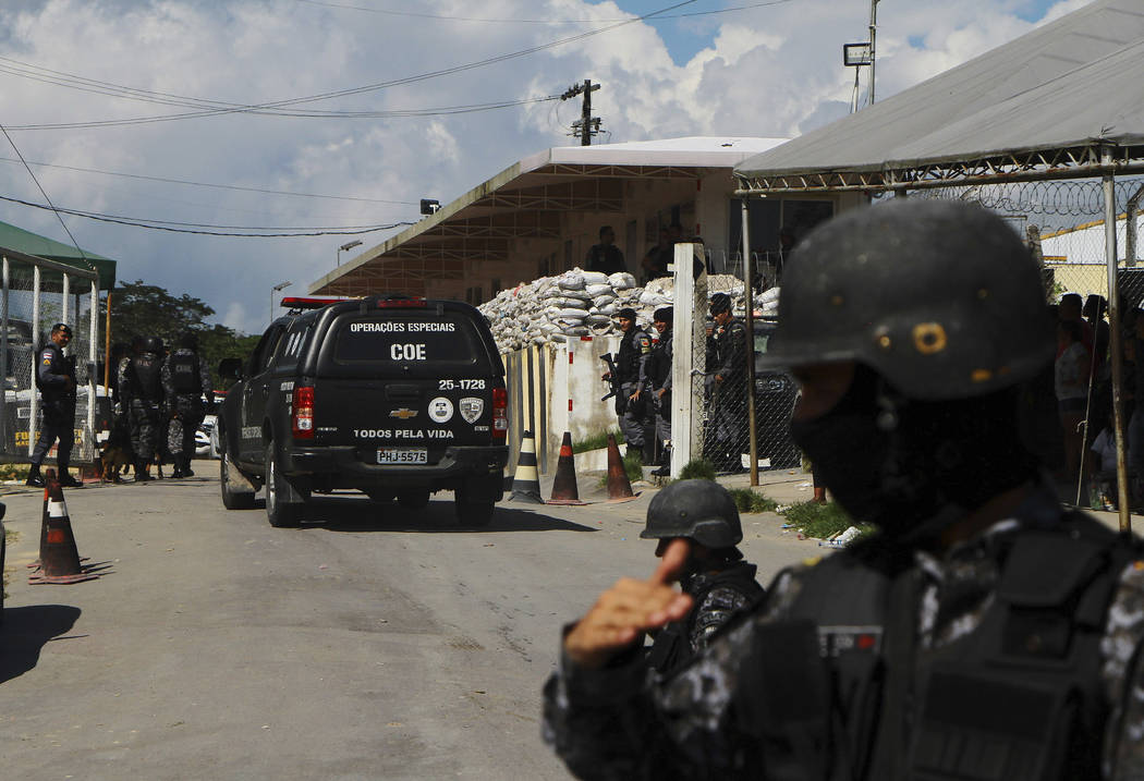 Police guard the entrance to the Anisio Jobim Prison Complex after a deadly riot erupted among ...