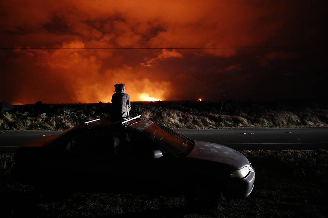 FILE - In this May 19, 2018 file photo, Brittany Kimball watches as lava erupts from a fissure ...