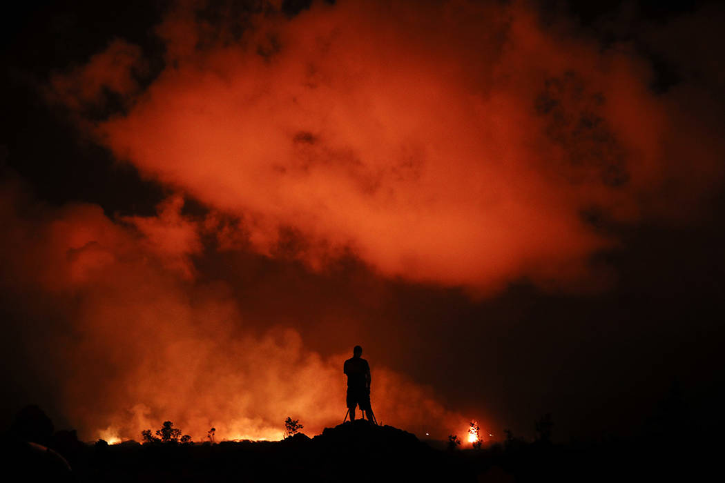 FILE - In this May 18, 2018 file photo, Peter Vance, 24, photographs lava erupting in the Leila ...