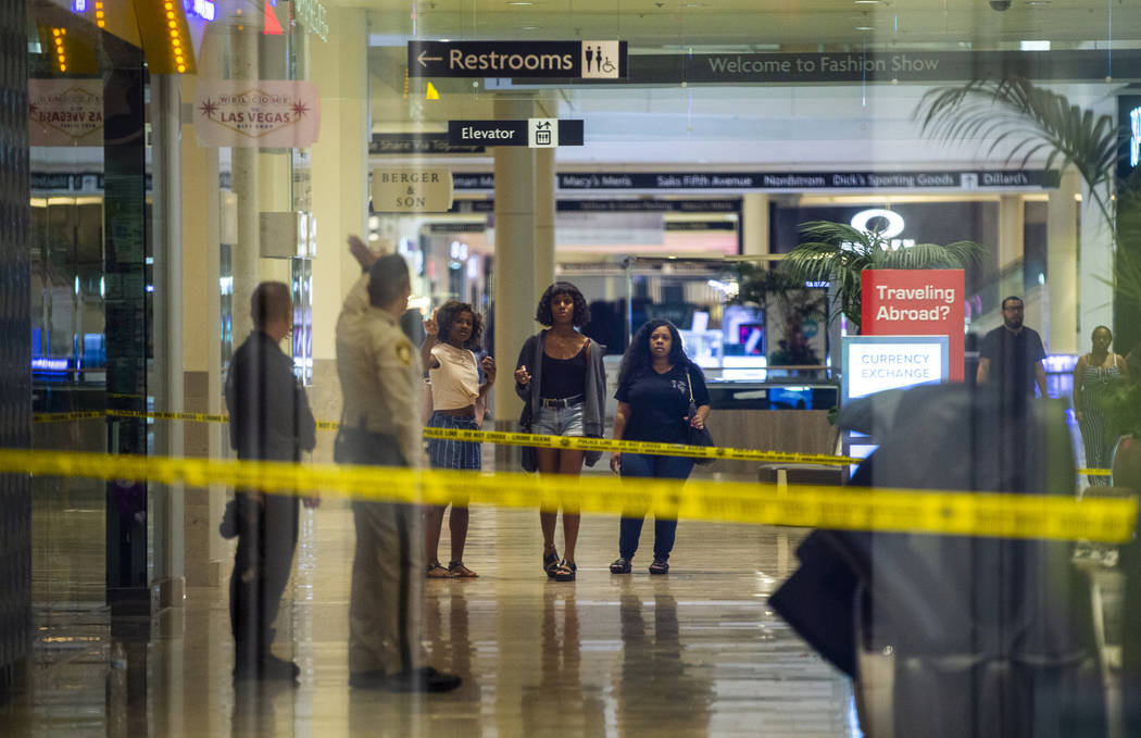 An LVMPD crime scene investigator and officer direct individuals inside the Fashion Show mall o ...