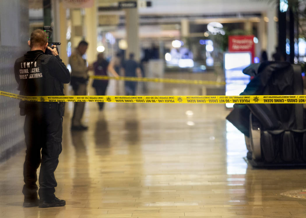 An LVMPD crime scene investigator shoots photographs inside the Fashion Show mall on the Strip ...