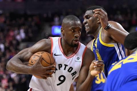 Toronto Raptors center Serge Ibaka (9) holds the ball as Golden State Warriors centre Kevon Loo ...