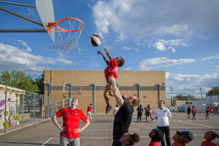 UNLV head basketball coach T.J. Otzelberger, middle, gives a boost to Ryan Fraley, 4, during a ...