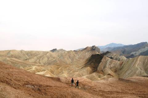 Hikers head across the badlands below Zabriskie Point in Death Valley National Park, California ...
