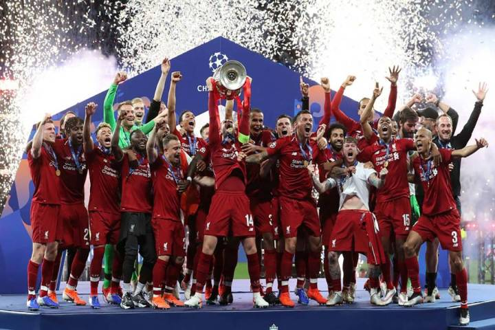 Liverpool's Jordan Henderson lifts the trophy to celebrate with his teammates winning the Champ ...