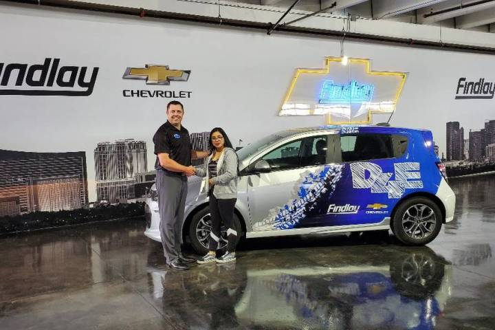 Findlay Chevrolet General Manager Doug Fleming congratulates Clark High School graduate Angela ...