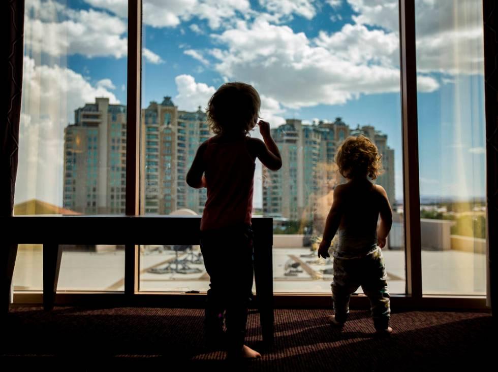 Dixie Baalman, 2, left, and Davie Baalman, 1, play in their family's hotel room at the Suncoast ...