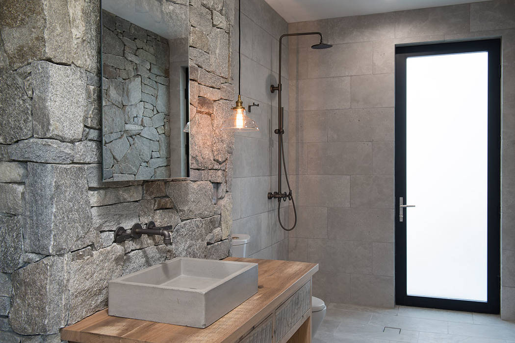 The master bath features lots of natural stone and wood. (Jewel Homes)