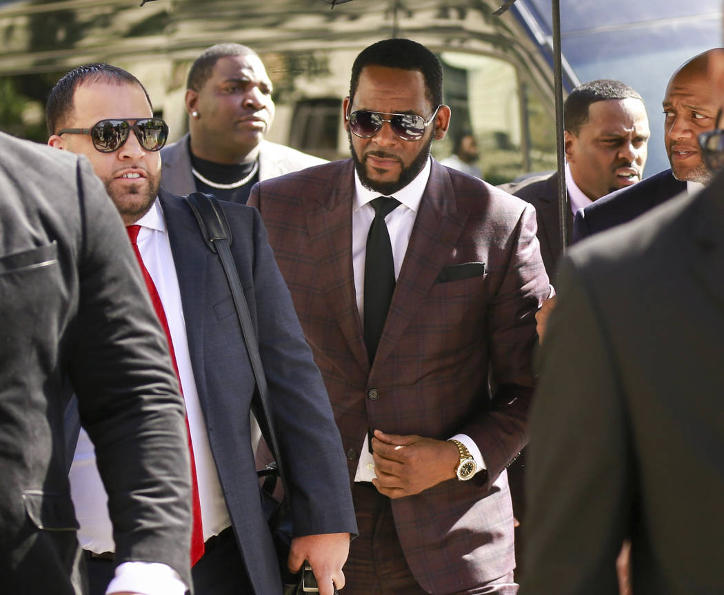 FILE - In this June 26, 2019, file photo, R&B singer R. Kelly, center, arrives at the Leigh ...