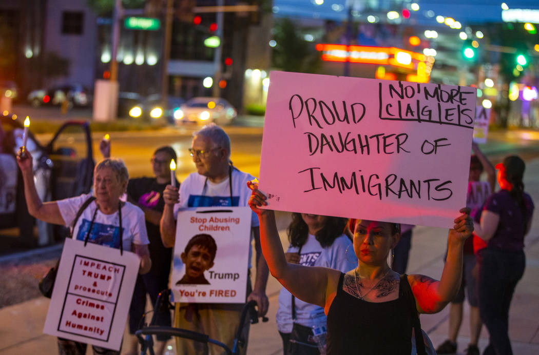 Activist Jessica Vasquez holds a sign for her parents during Lights for Liberty: A Vigil to End ...