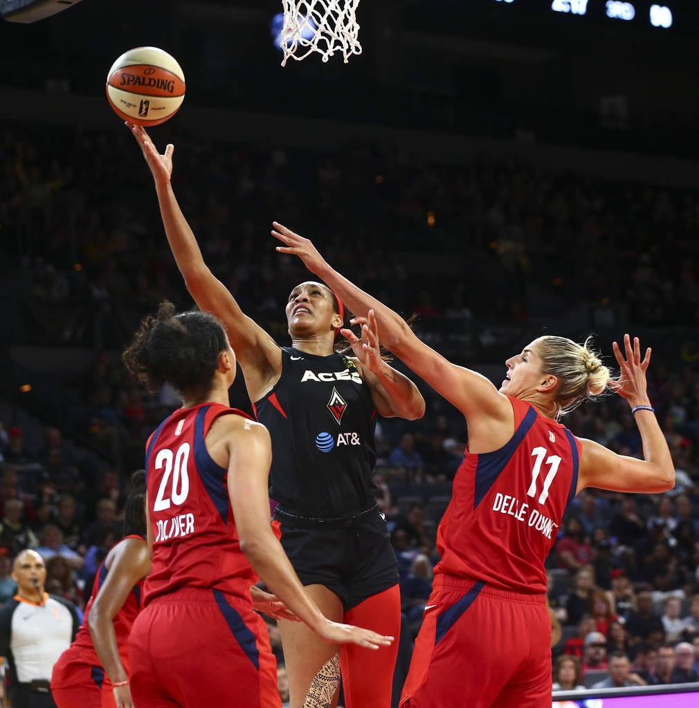 Las Vegas Aces center A'ja Wilson (22) goes to the basket between Washington Mystics guard Kris ...