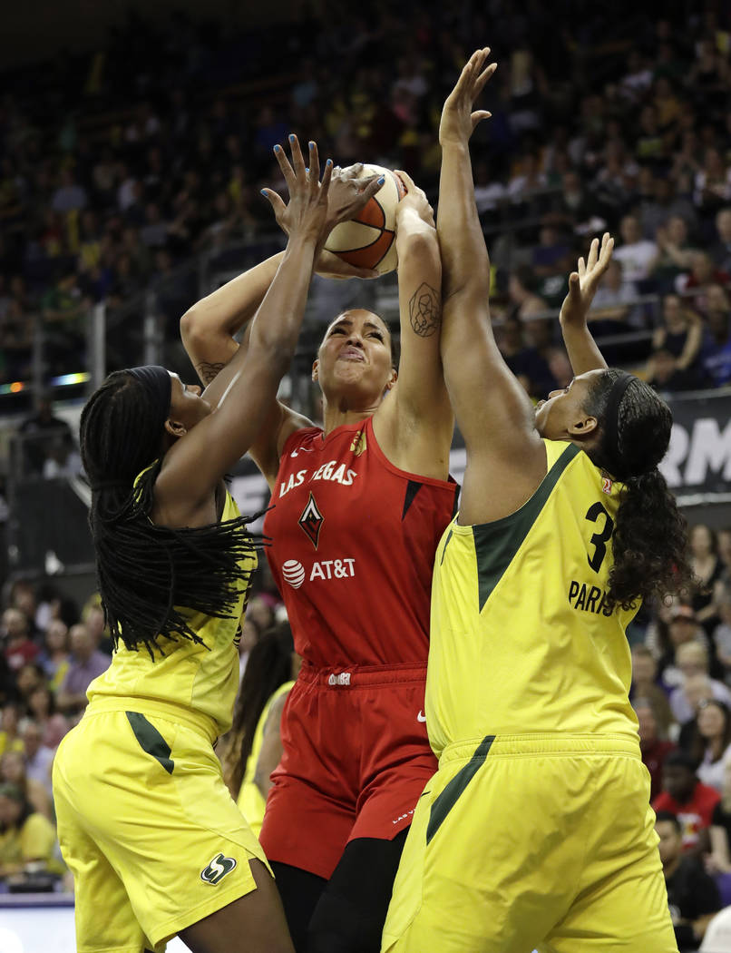 Las Vegas Aces' Liz Cambage, center, is doubled-teamed by Seattle Storm's Crystal Langhorne, le ...