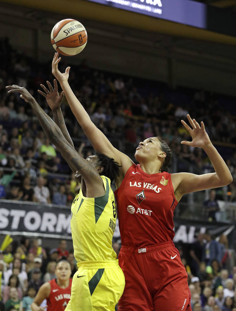 Las Vegas Aces' Liz Cambage, right, reaches for a loose ball over Seattle Storm's Natasha Howar ...