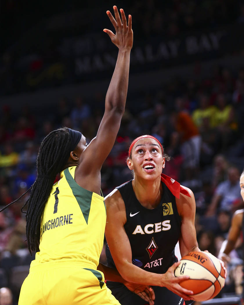 Las Vegas Aces' Dearica Hamby looks to shoot under pressure from Seattle Storm's Crystal Langho ...