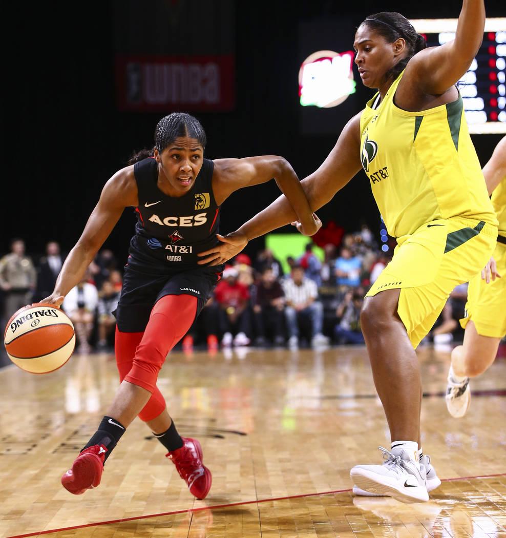 Las Vegas Aces' Sydney Colson, left, drives to the basket against Seattle Storm's Courtney Pari ...