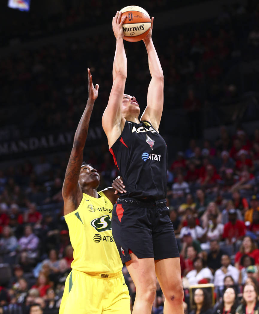 Las Vegas Aces' Dearica Hamby gets a rebound in front of Seattle Storm's Natasha Howard during ...