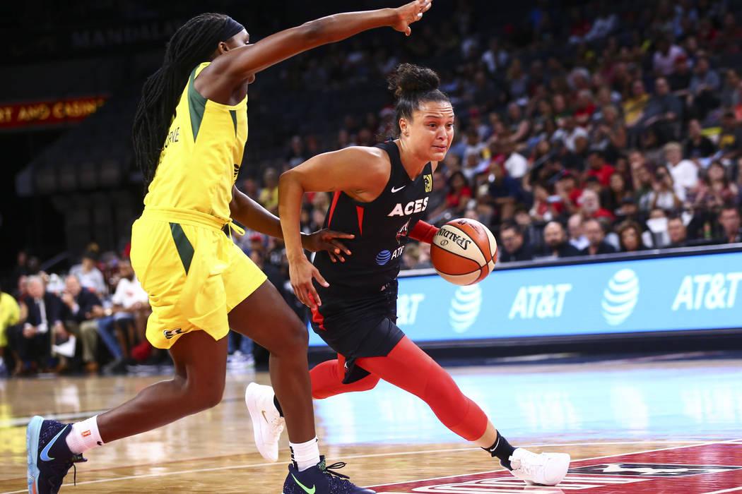 Las Vegas Aces' Kayla McBride drives to the basket past Seattle Storm's forward Crystal Langhor ...