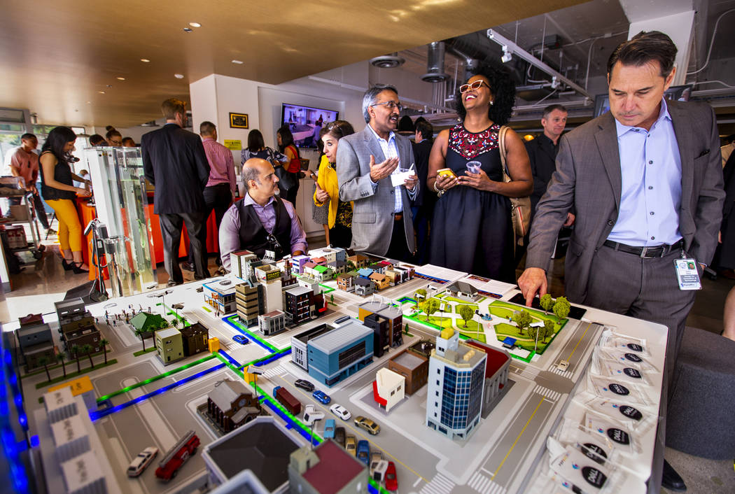 Attendees talk about the uses of an NTT Smart City Platform demonstrated on a model during the ...