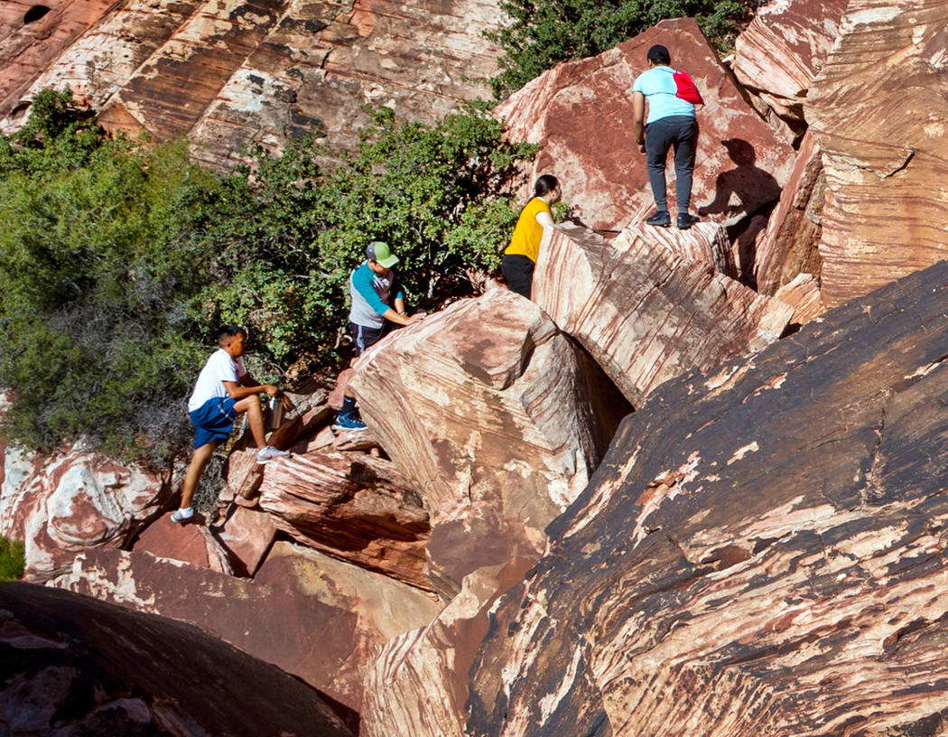 Visitors climb in the Calico 1 area within the Red Rock Canyon National Conservation Area, west ...