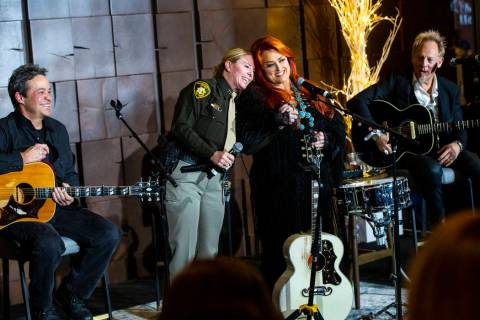 Metropolitan Police Department Capt. Kelly McMahill, second from left, embraces singer-songwrit ...