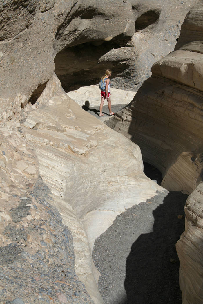A hiker heads through a narrow section of Mosaic Canyon in Death Valley National Park, Californ ...