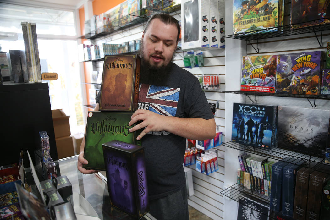 Ryan Champion, co-owner of The Gaming Goat, shows a board game for sale inside his business at ...