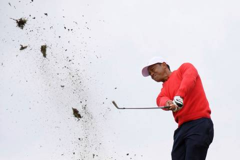 Debris flies as U.S. team player and captain Tiger Woods plays a shot on the 10th raiway in his ...